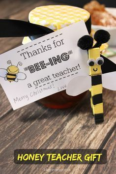 """Honey BEE Teacher Gift with Free Printable Tag. Put a smile on an educator's face this holiday season with this """"Thanks for """"BEE-ING"""" a great teacher"""" honey jar gift! A cute DIY clothespin bumblebee and a yellow houndstooth cloth jar topper tied with a black ribbon really make this present shine! #HoneyForHolidays #ad"""
