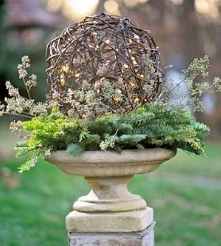 This birdbath is lined with a fresh pine wreath and topped with a vine ball. To add sparkle, thread a strand of battery-powered white lights into the ball. (BH&G)