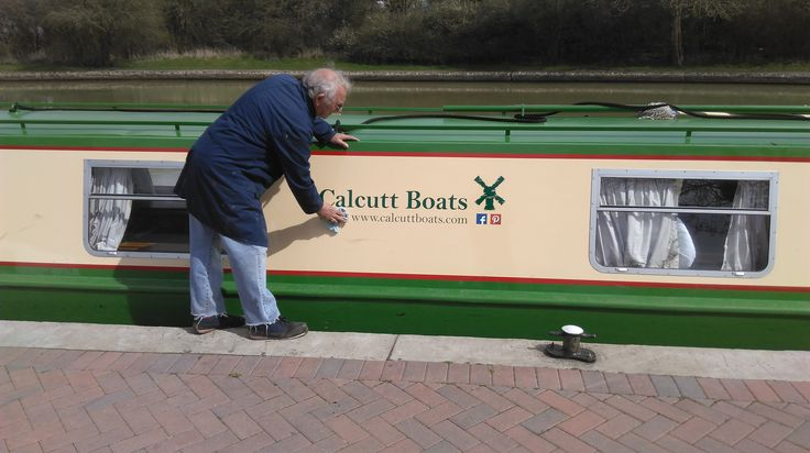 Stuart applying the finishing touches to the new Calcutt Boats hire fleet graphics.