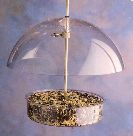 """X1  Seed Saver. Small covered dish feeder. Adjustable dome. 7"""" diameter. Capacity of .75lbs. Lifetime warranty. Brass rod for hanging.. UV stabilized polycarbonate."""