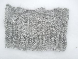"""This is a lace cowl using a variation on the Frost Flower stitch pattern. It makes an excellent, warm, soft accessory when knit from handspun Angora! The Angora I used was sport weight and you could get beautiful results from a sport weight commercial yarn - something like Knitted Wit or Hazel Knits. Gauge is not important, but I found that I liked the resulting fabric best using size 8 needles (I originally tried size 10). The finished size is approximately 22"""" x 10""""."""