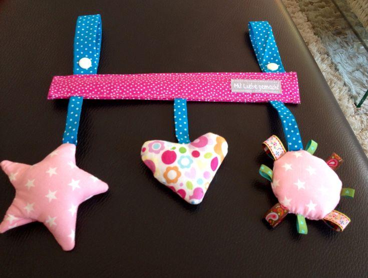 MaxiCosi Spielzeug Der Stern knistert, im Herz ist eine Rassel und in dem Runden rechts ist eine Quietsche