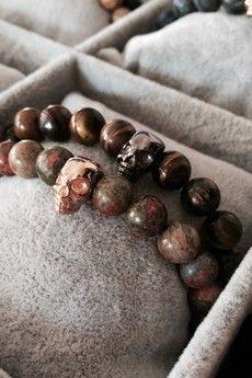 Dizarro to męska biżuteria najwyższej jakości produkowana z kamieni półszlachetnych, srebra, złota oraz kryształów Swarovski™.  Świąteczny zestaw! 2 bransoletki wykonane z brązowego tygrysiego oka i zielonych jaspisów z czaszką z rutenowanego srebra 925 oraz pokrytą 23-karatowym włoskim złotem.Szczegóły:- czaszki srebro rutenowane 925