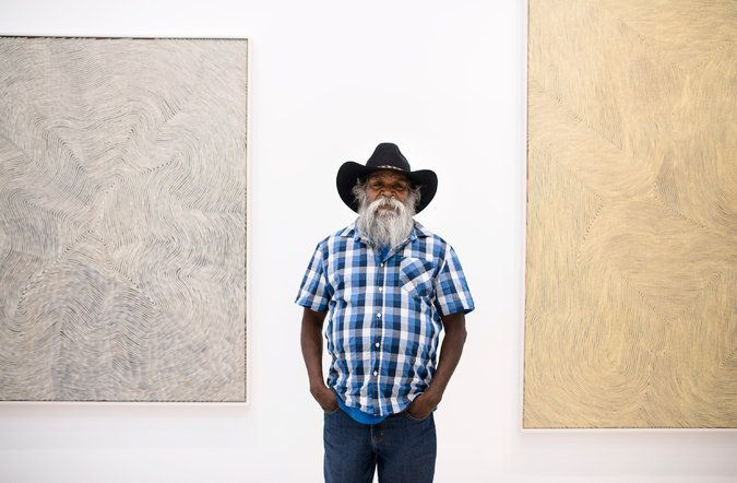 Warlimpirrnga Tjapaltjarri with two of his untitled paintings at Salon 94.  An Aboriginal Artist's Dizzying New York Moment - The New York Times