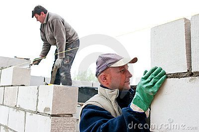 Two masons building new wall with white bricks.
