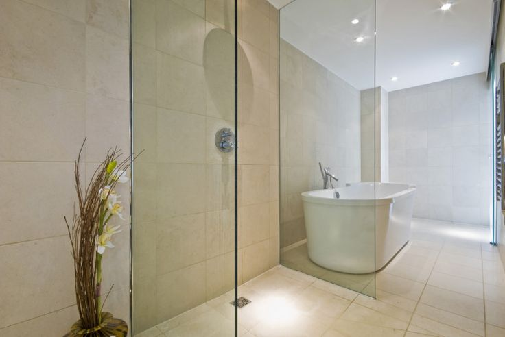 Contemporary bathroom with large bathing tub and almost open plan style shower cabin with glass panels each side and no door