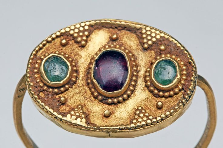 Viking gold ring; oval face with central garnet cabochon surrounded by a pair of emerald cabochons, all highlighted with fine granulation, the gold granules surrounding the cabochons and perimeter of the face, as well as arranged in triangular motifs for additional interest. Perhaps intended as a swivel ring; however, swivel does not rotate 360 degrees. Viking women (and men) wore precious jewelry such as this example as a symbol of status. //  found in Britain, ca. 9th to 12th centuries CE.