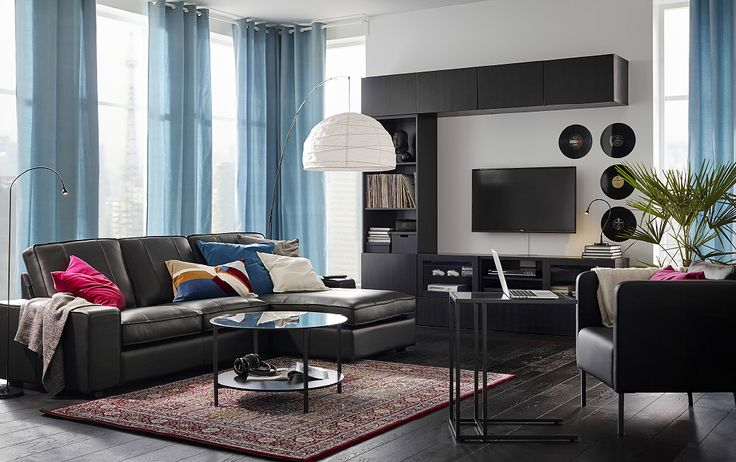 A living room furnished with a black two-seat sofa in leather combined with a chaise longue. Shown together with a round coffee table with a glass top and a black leather armchair.
