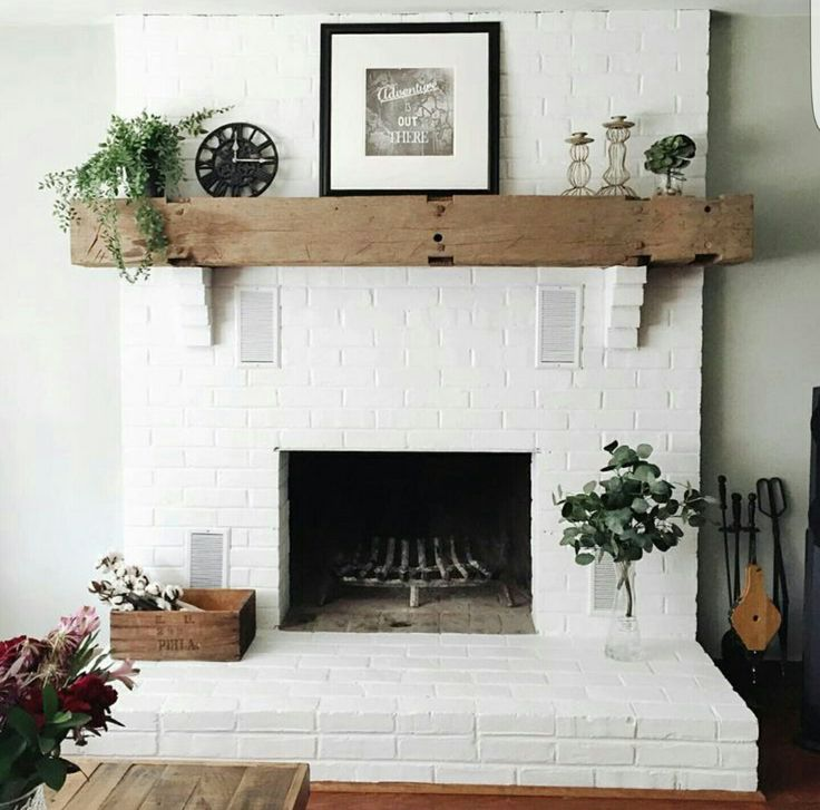 Brick fireplace painted white with a cedar mantle