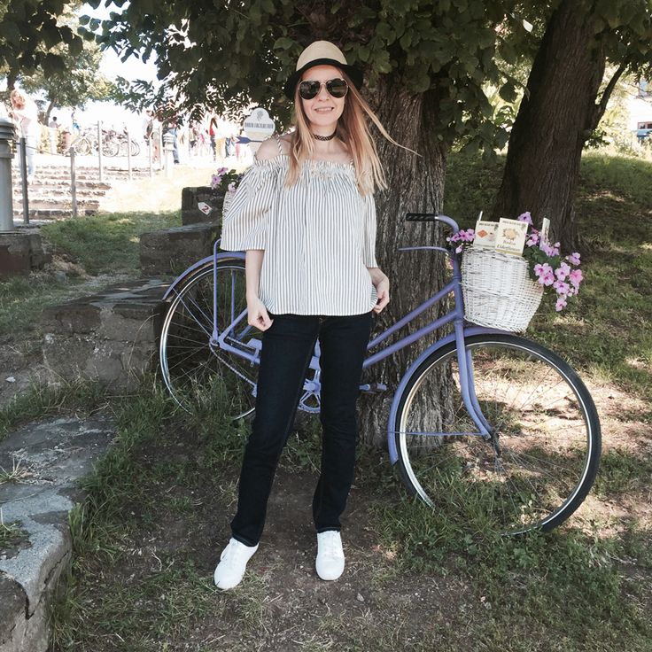 off-shoulder striped top, indigo slim straight jeans, white trainers, straw trilby, Nineties nylon choker, aviators, lavender bicycle
