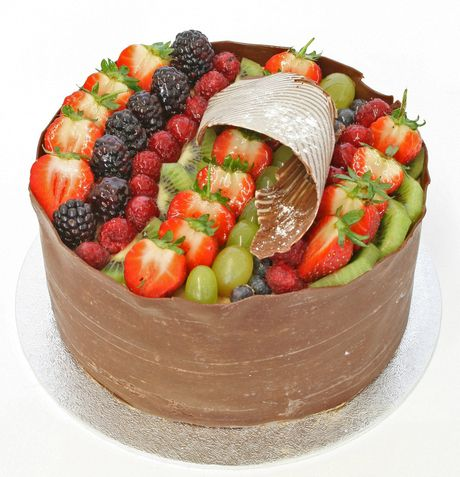 Gateau Elysees: The light, moist sponge filling is split with delicious crème patisserie and decorated in a handmade chocolate casing to the sides and chocolate curl on top. The cake is filled with market fresh mixed fruits. It really does taste as light and delicious as it looks