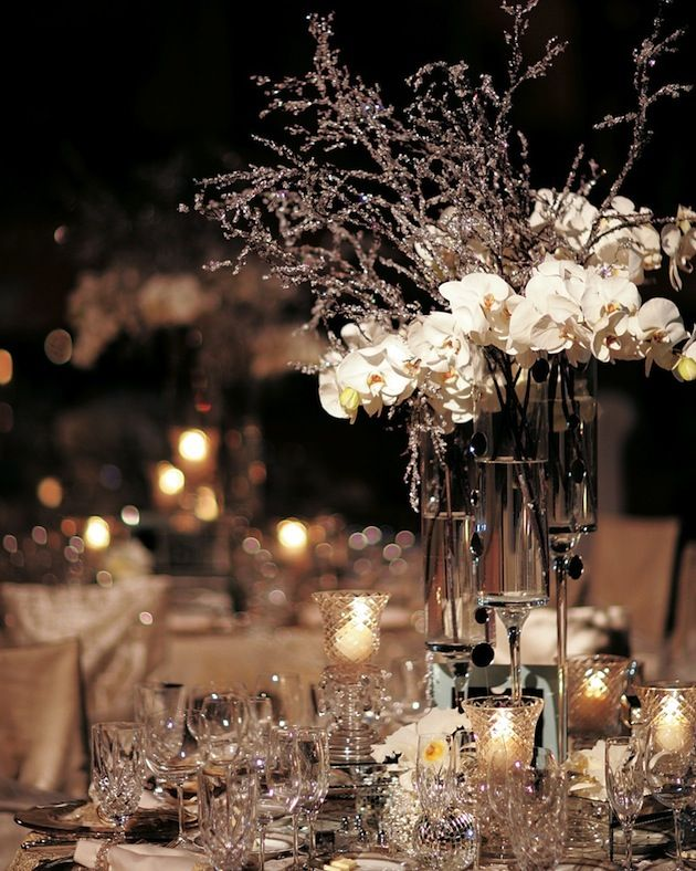 buy different size glasses glue different size candle holders to the bottom and put the branches in them as a vase and hang the snowflakes.
