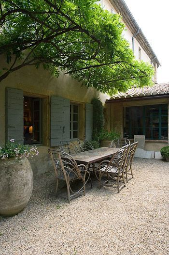 Elegant French country courtyard with rustic outdoor dining set, and painted blue shutters on the house behind.