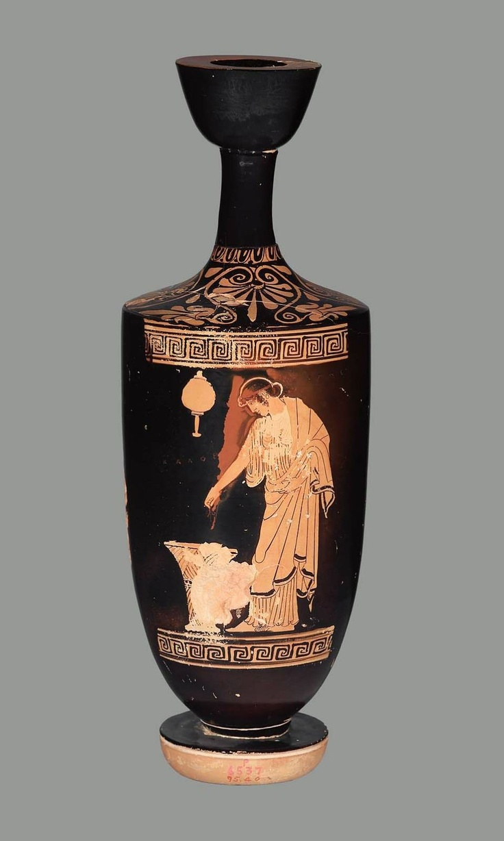 """Oil flask (lekythos) with a maiden  Greek, Classical Period, about 470–460 B.C.  the Telephos Painter,  PLACE OF MANUFACTURE  Athens, Attica, Greece  A maiden, profile to left, stands looking down into a tall basket in which she drops a flower.     In the field, the Greek inscription """"Lihas is handsome"""" (Lihas Kalos). The word Lihas to the right of her head, the word Kalos beneath the mirror to the left of her head."""