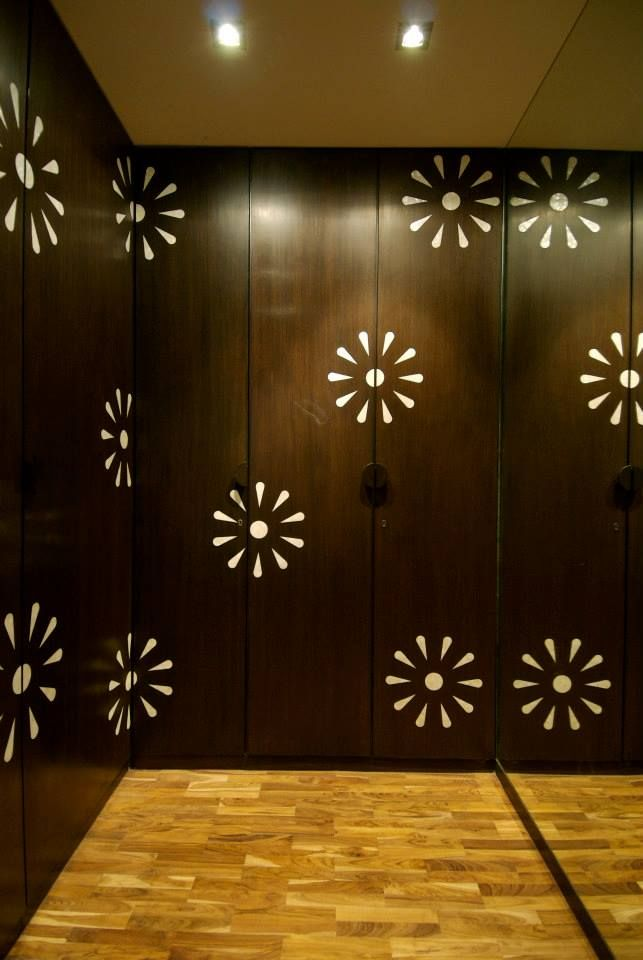 An ancient Indian art of inlaying precious stone in wooden surface has been employed to embellish these mother of pearl graphical flowers in the walk-in wardrobe shutters adding a hint of delicacy to them in this duplex apartment interior design project at Mumbai.