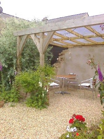 Attached lean-to pergola with climbing plants.