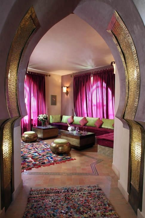 A modern twist on Moroccan arches. Hand hammered brass screens molded into the arches shape. Golden poufs and Boucherouite rag rugs. #Moroccanarches #Boucherouite #Poufs.