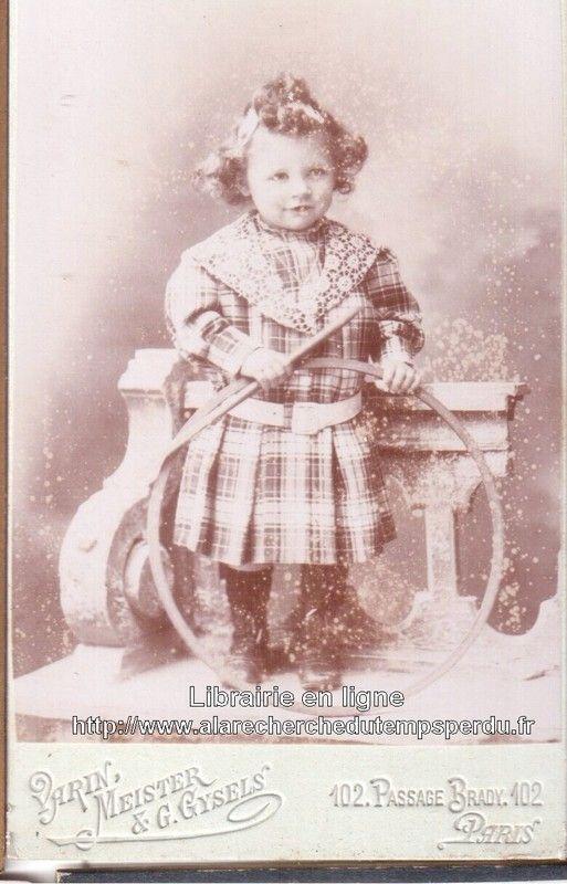 Petite fille parisienne tenant un cerceau dans les mains. Elle porte