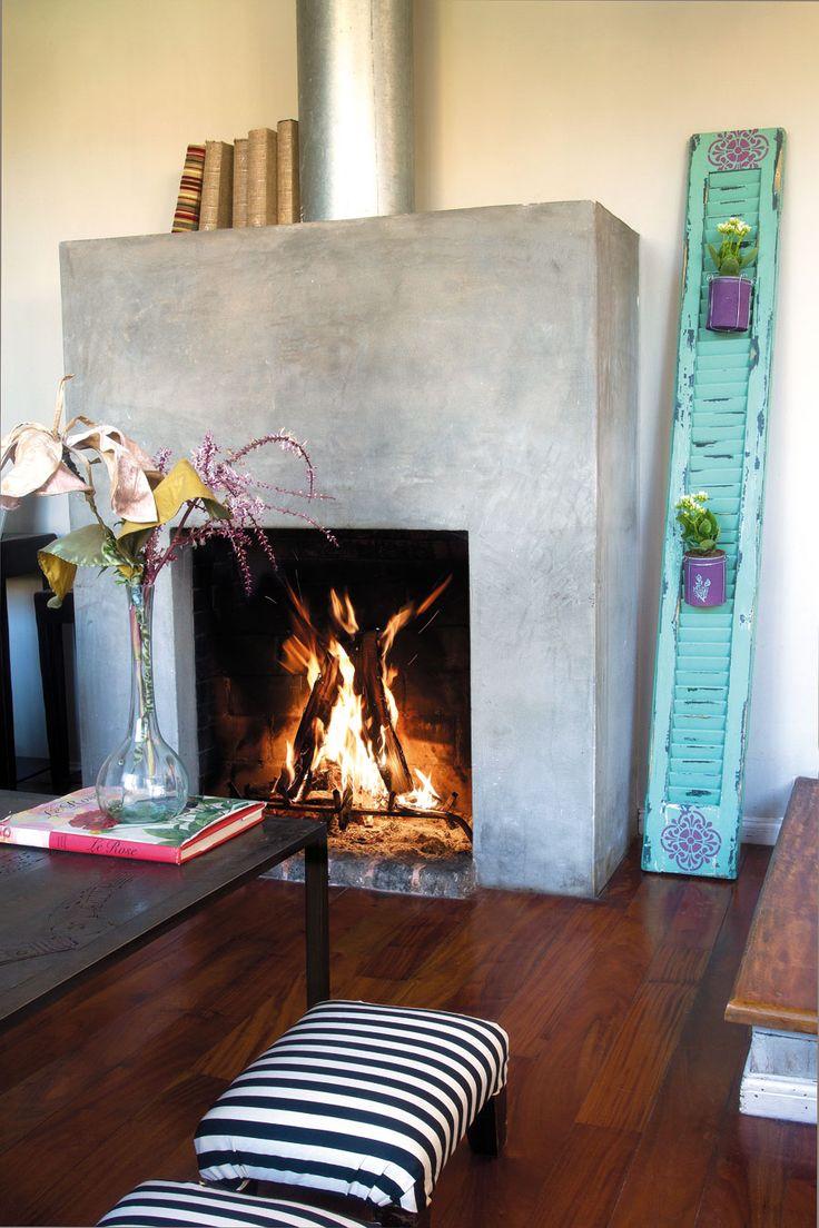 En otro ángulo se aprecia la chimenea con estructura en cemento alisado, centro de reuniones al calor del fuego. Sobre el piso de madera se recorta una mesa de chapa negra de líneas simples y unos banquitos (ambos de Colores) retapizados por la dueña de casa con tela a rayas. Un antiguo postigo con macetas (Lucila Ardizzone) se vuelve objeto decorativo contra la pared e imprime el infaltable sello color aqua, pieza clave en el ADN decorativo de la casa.