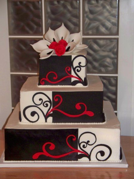 Buttercream frosted red velvet cake with mousse filling.  Black fondant panels with scrollwork from the bride's invitation.  Sugar Calla lilies and roses.