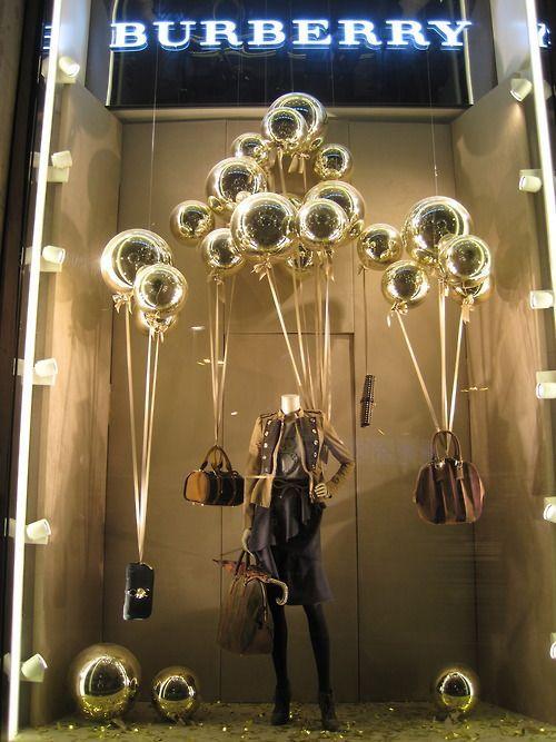 """Burberry lancia una campagna d'oro di marketing natalizio per celebrare Londra, la britannicità e il tempo. Dalle vetrine risplende il colore oro dei palloncini, chiamati """"Golden balls…"""