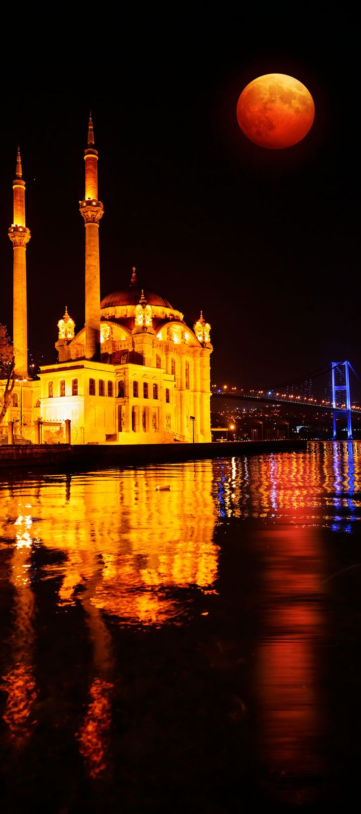 Scenic View of Ortakoy Mosque and Bosphorus Bridge with Lunar eclipse Istanbul, Turkey
