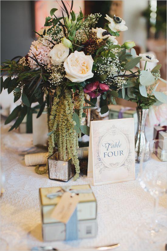 Classic cascading centerpiece with book themed table number. #weddingchicks Captured By: Mango Studios http://www.weddingchicks.com/2014/06/25/indoor-garden-party-bridal-shower/