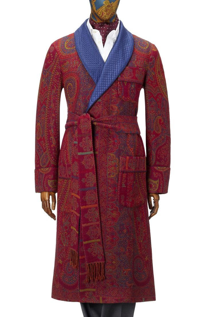 This luxurious gown has been inspired by vintage pieces from the 1920s. Made by cutting four wool & silk throws woven in a rich tapestry design and then carefully reconstructing the pieces in a gown format it is a work of art and the pinnacle of workmanship. Fully lined in maroon silk featuring a quilted shawl collar and gauntlet cuff it features slash pockets and an out breast welt. Made in England.