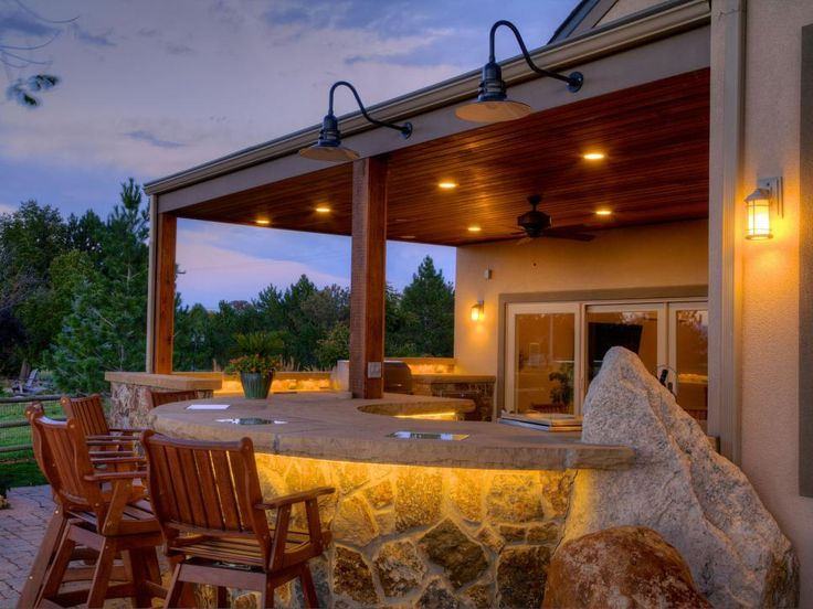 An outdoor deck with a built-in bar and dining area becomes a mellow, laid-back hangout at night due to the artful lighting design.