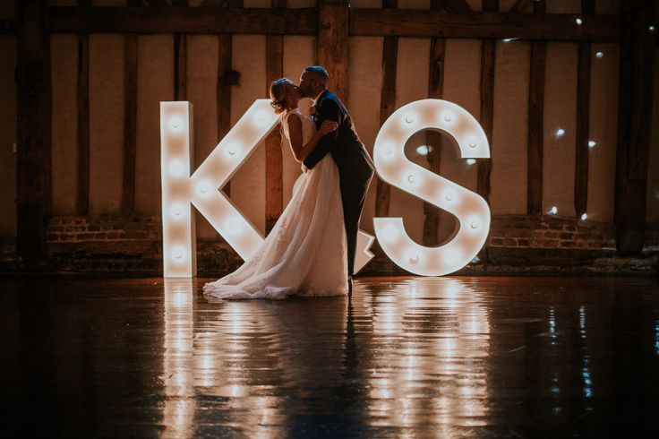 Large letters light up the dancefloor for the first dance in the Essex Barn. Blake Hall Weddings. Keeley & Stuart by D&A Photography, a Contemporary UK & Destination Wedding Photographer