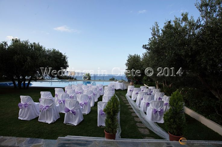 Weddings in Crete - Flower Arrangement and Chairs with White Covers and Lilac Bows Chania area