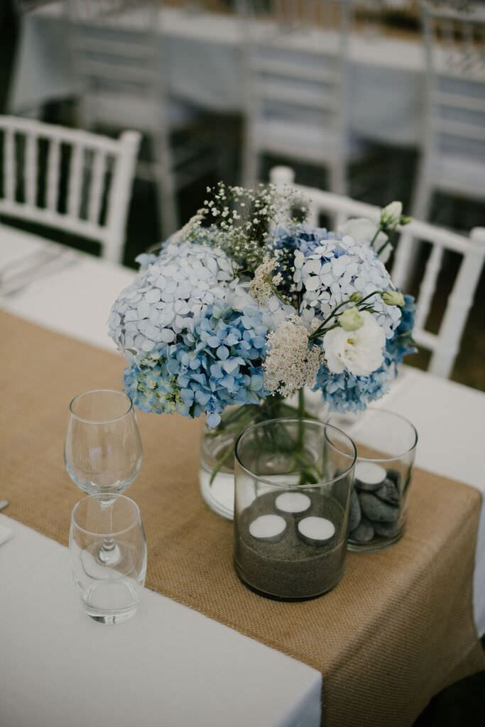 Blue color wedding theme for a stunning rustic beach wedding in new rustic beach wedding burlap table runnerdriftwood pebbles sand and blue hydrangea wedding centerpieces beachwedding wedding rusticwedding junglespirit Gallery