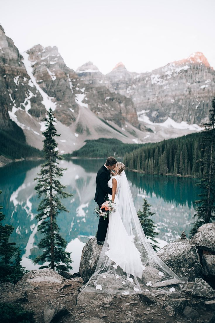 Bride and groom at Moraine Lake, Banff National Park with coral and burgundy bridal bouquet. Photo: Duke Moose Bouquet: Flowers by Janie