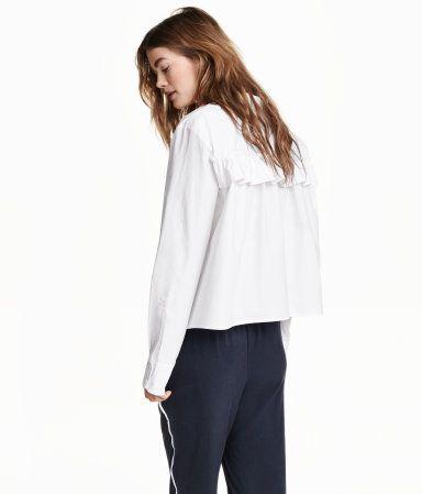 Een wijde blouse van katoenen popeline met een decoratieve volant aan de achterkant. De blouse heeft lange mouwen, een knoopsluiting voor en een borstzak. Licht afgerond aan de onderkant.