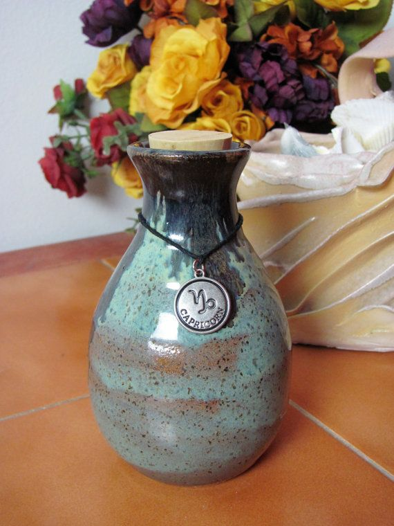 This is a handmade wheel thrown corked bottle. The glaze a light blue with accents of brown and dark blue. The bottle is adorned with the Capricorn Zodiac symbol. Customers can request different zodiac symbol if they choose. Please leave a comment upon purchase specifying which zodiac symbol you would like. This item is food safe, microwave and dishwasher safe.  Size: 5.5in tall