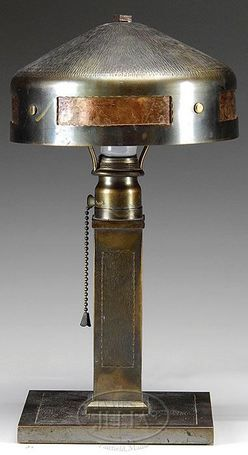 A Roycroft hammered copper and mica helmet-shade [arts & crafts table] lamp, first quarter 20th century. New York. The helmet-shaped shade with rectangular tea-stained mica panels are fastened with brass rivets, joined to the base with square standard joined to a flat square plinth all hammered. Base of standard with orb and cross mark. Craftsman bungalow; Mission style