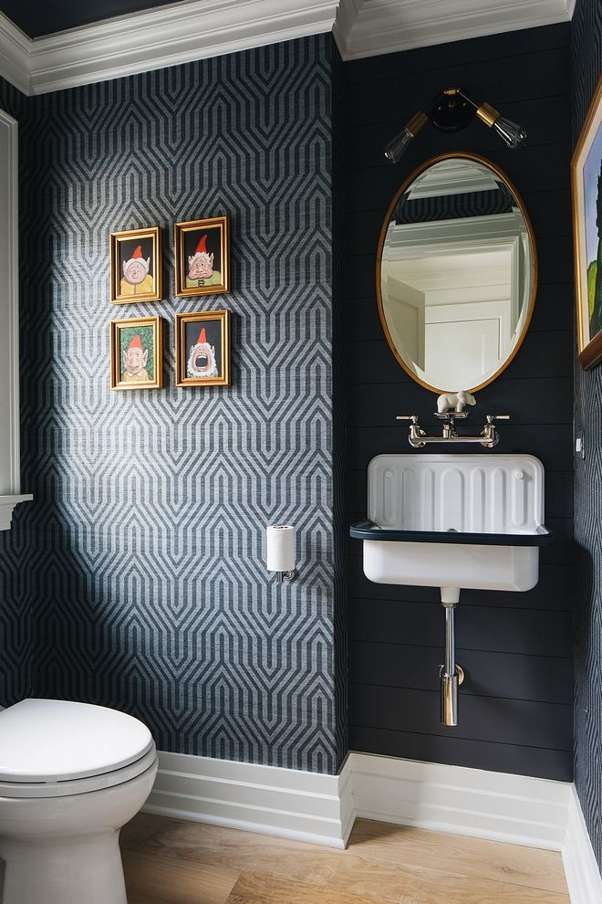 Black shiplap This powder room features a dramatic…