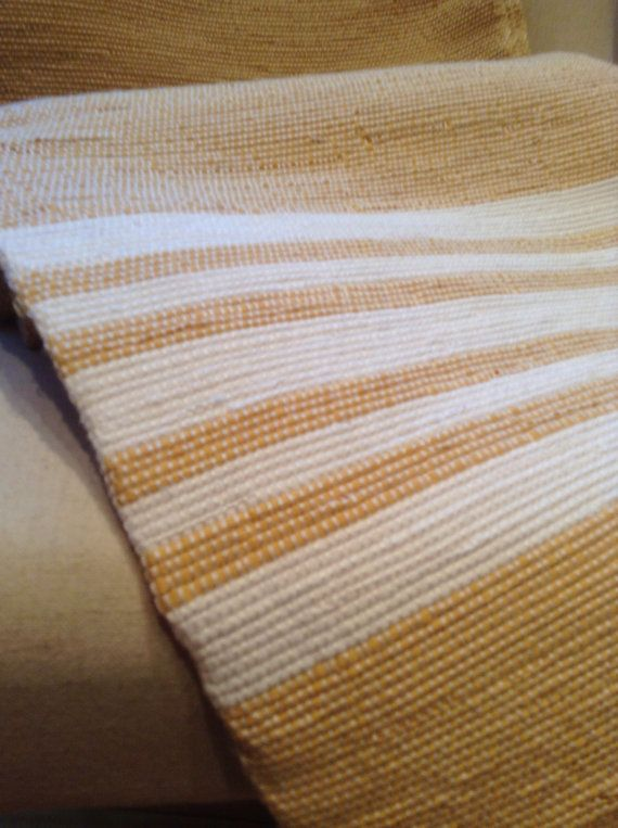 This handwoven twin size blanket known as a catalogne, is done in a soft buttercup colour accented with white stripes at one end. It measures 57 wide X 96 long. Fabricated on a traditional floor loom, it is unique and of artisan quality. Gentle machine washing and hanging it to dry will keep it looking its best for generations to come.