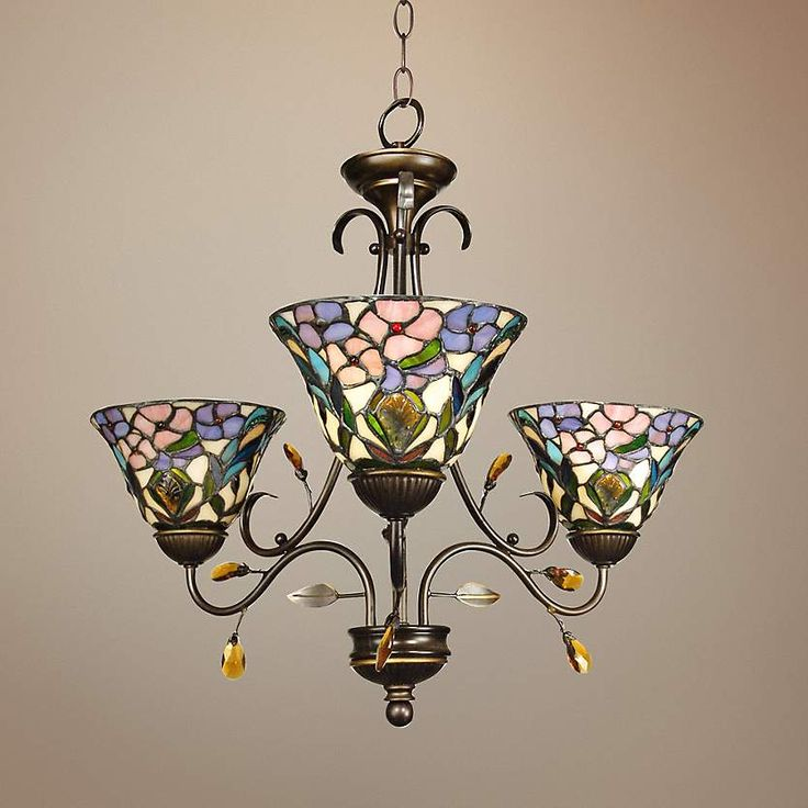 3 art glass shades with a peony motif are complemented by scrolling arms paired with leafy accents.