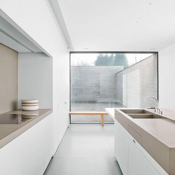 Vincent Van Duysen White modern kitchen. Clean lines, beige countertop, big window.