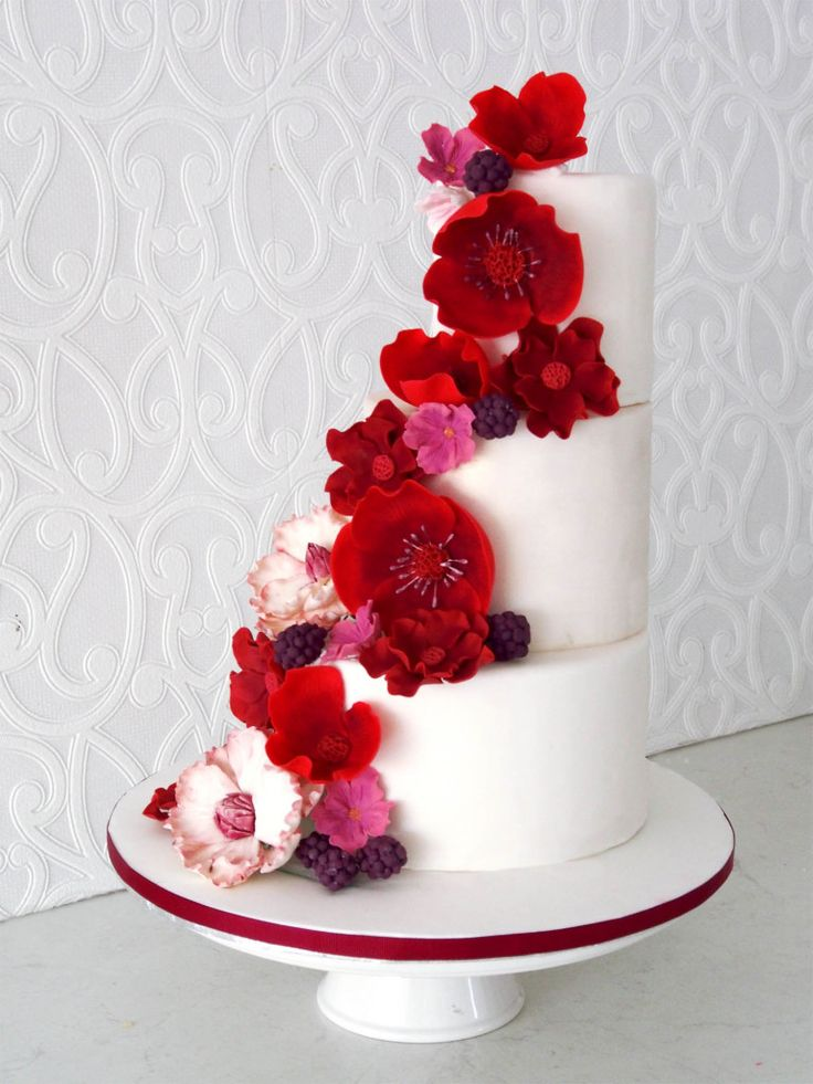 Right aligned tiers of fondant decorated with cascading red sugar flowers.