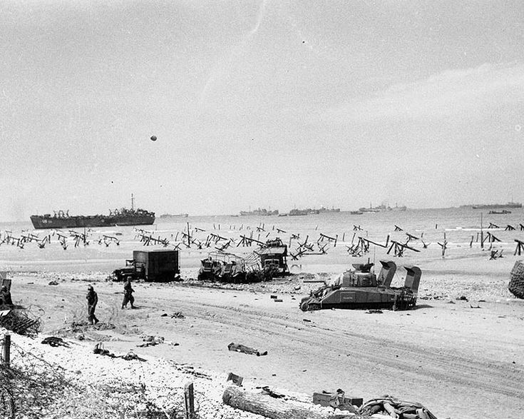 """Scene on """"Omaha"""" Beach on the afternoon of """"D-Day"""", 6 June 1944, showing casualties on the beach, a bogged-down """"Sherman"""" tank, several wrecked trucks and German anti-landing obstructions. A LST is beached in the left distance and invasion shipping is off shore."""