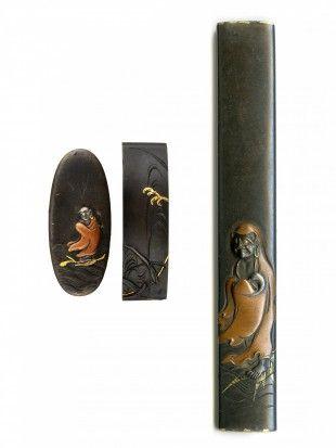 72 Fuchi, Kashira Und Kozuka Japan Kupferlegierung. L 3,4 cm - 9,8 cm.   Provenienz: Carlo Monzino (1931-1996), Castagnola.  Kashira: Daruma darstellend. Fuchi: Gewässer und Schilf. Gemäss Sotheby's London (Juni 1996, Lot 108): Edo-Zeit (18. Jh.). Kupferlegierung, Details in Gold.  Kozuka: Daruma darstellend. Kupferlegierung, Details in Gold. Signiert.