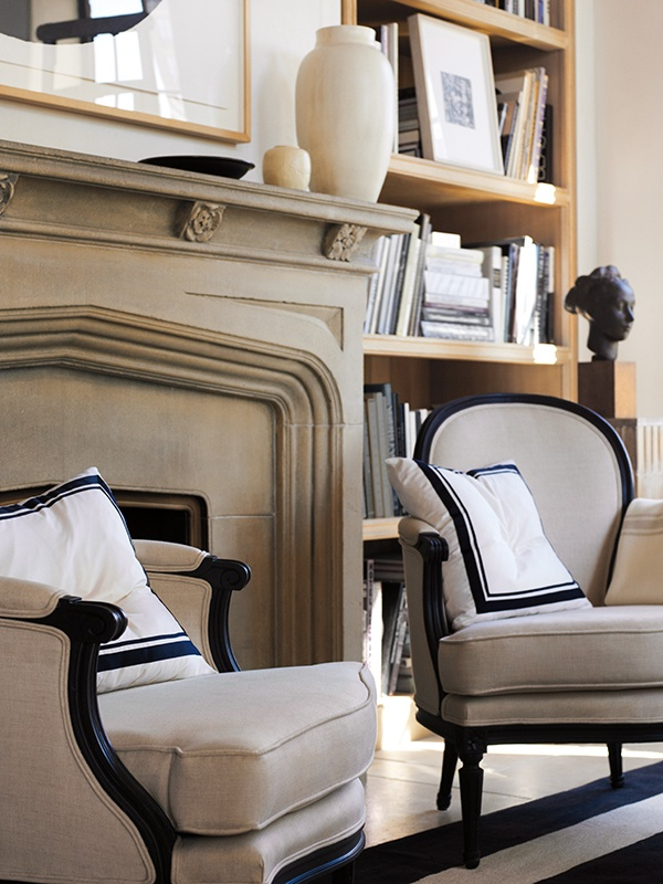 Tudor arch fireplace, natural linen colored chairs with black frames -- photo: Jo Malone™ Home Collection (candles)