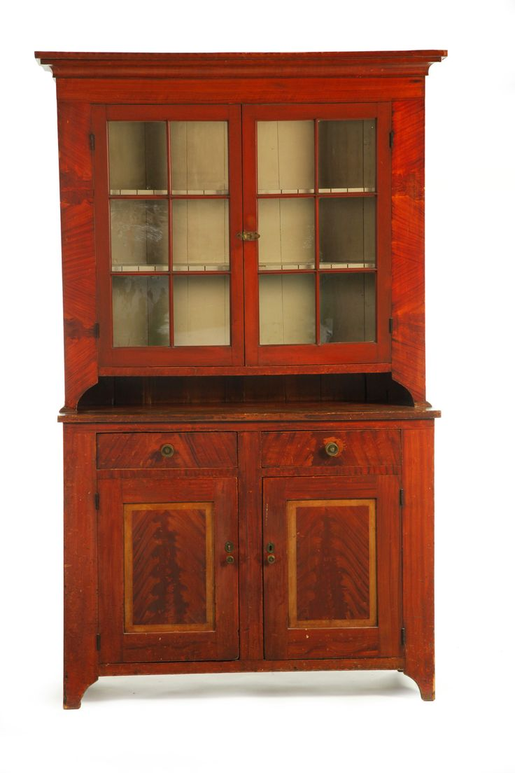 """DECORATED STEPBACK CUPBOARD -    Pennsylvania, early 19th century, pine. Two-piece cupboard: the upper section with two six-pane doors and interior shelves with plate grooves and spoon slots, the lower section with two drawers over two doors and cutout bracket feet. Retains its original red paint with black graining and yellow trim on the lower doors to mimic raised panels. 88""""h. 55""""w. 20""""d."""