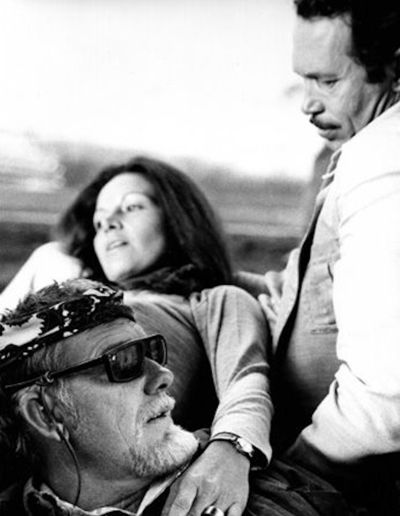 BRING ME THE HEAD OF ALFREDO GARCIA - Director Sam Peckinpah discusses a scene with Warren Oates. That's Isela Vega behind Peckinpah - MGM - Publicity Still.