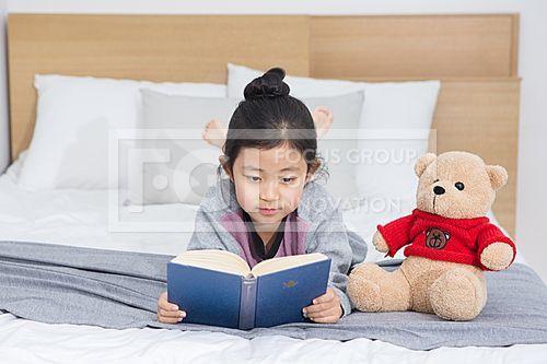 여자 어린이 413,PHO383, 프리진, 사진, 여자, 어린이, 에프지아이, 컨셉, 프리진, PHO383, PHO383f, 사람, 어린아이, 아이, 여성, 여자아이, 여자어린이, 초등학생, 어린, 소녀, 귀여운, 동양인, 아시아, 대한민국, 한국인, 1인, 한명, 스튜디오, 실내, 침실, 침대, 베개, 이불, 푹신한, 기대있는, 편안한, 여유로운, 책, 읽고있는, 잡고있는, 들고있는, 인형, 엎드린, 미소, 웃음, 집중, 집중한 #유토이미지