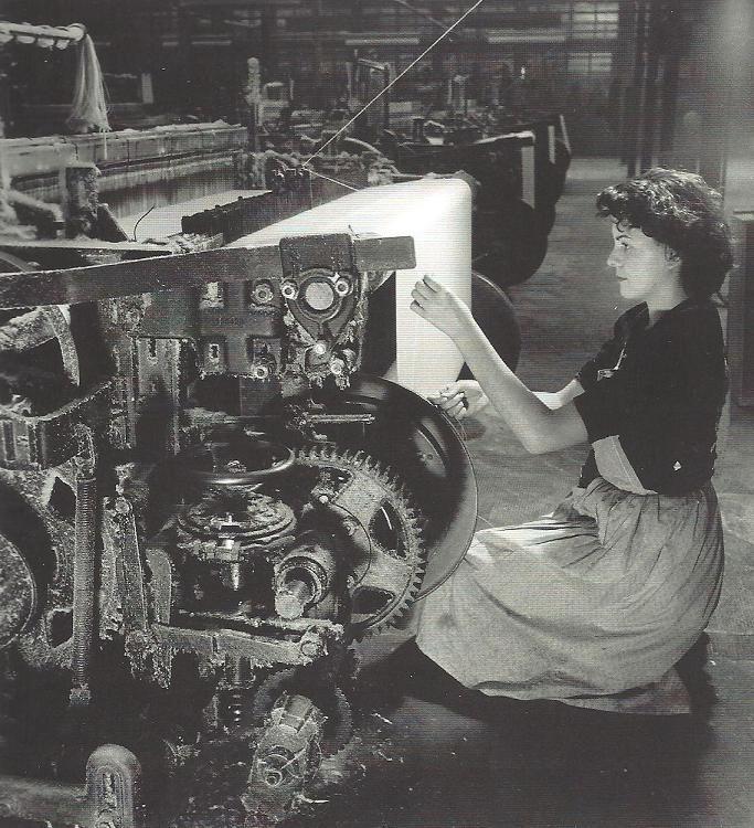 Willy Ronis - Le fil cassé, 1950 - 1950: Ronis sta realizzando un reportage in una fabbrica tessile dell'Haut-Rhin: mentre il suo accompagnatore gli illustra la vita dello stabilimento, egli nota una ragazza inginocchiata davanti al telaio. La sua bellezza, la grazia con cui cerca di riannodare un filo spezzato evocano in lui l'immagine di un'arpista davanti al suo strumento.