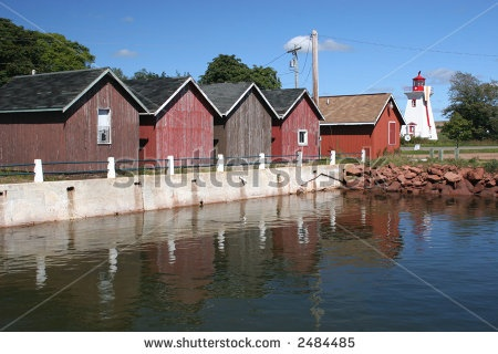 Fishing shacks  and lighthouse at the wharf in Victoria-by-the-Sea, Prince Edward Island. by V. J. Matthew, via ShutterStock