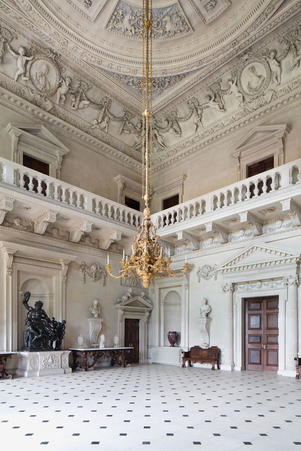 The Stone Hall at Houghton Hall, Norfolk, England. Commissioned by Robert Walpole, the first real prime minister, Houghton represented the grand English Palladian tradition as interpreted by Colen Campbell and William Kent. A plentiful serving of original furniture and art remain in tact, including the magnificent interiors that make up the mansion. Just to give you an idea of the scale of this room, your head would only reach a few feet above the height of the original benches.~